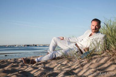 Gabe LaDuke wearing a suit lying on a sandy beach
