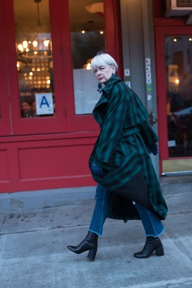 grey haired woman in grren plaid coat in front of red building
