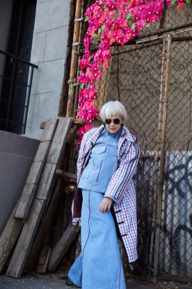 Grey haired woman in light blue skirt suit and plaid overcoat