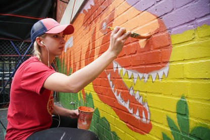 blonde woman in ball cap painting dinosaur on brick wall