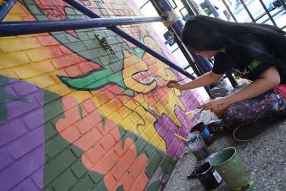 woman paints mural