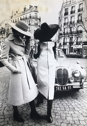 Two models posing on the streets of Paris, in large brimmed suede and felt hats, paired with a belted, wool, knee length coat and a vinyl, knee length, raincoat, over dark colored pants and shoes