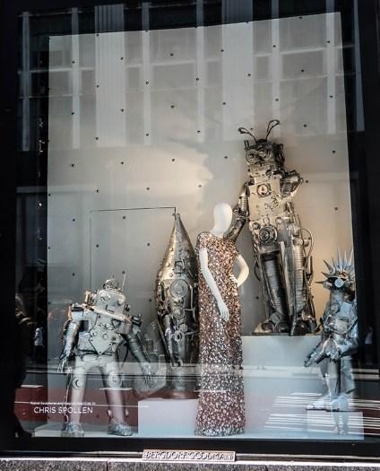 mannequin in sequin dresses with metal robot sculptures