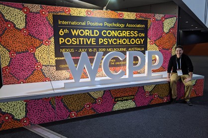 Daniel Benkendorf sitting in front of World Congress on Positive Psychology sign