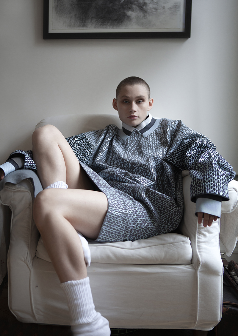 young woman with shaved head sitting on armchair in slouchy sweater dress