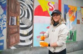 Young woman painting mural