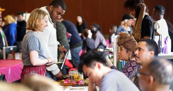 Students look at colorful floral crafts; a women in a headscarf sits at table describing her wares.