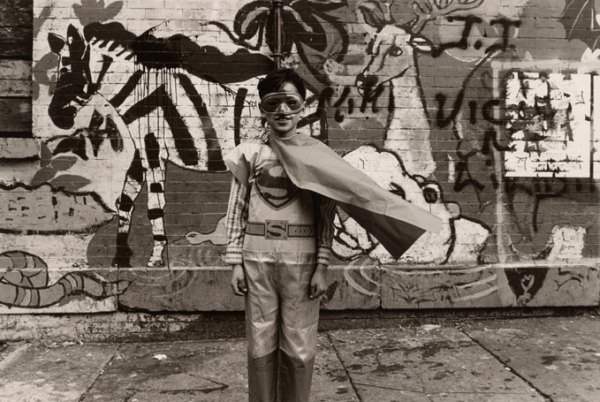 A young boy in wears a Superman costume and stands in front of a graffiti-tagged wall
