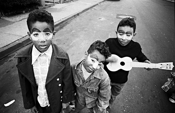 Three boys wearing tear makeup for Halloween. One boy holds a toy guitar.