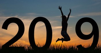 The numbers for 2019 in the sunset with a womn jumping in the place of the 1.