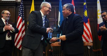 John Briggs shake hands with Archbishop Bernardito Auza on stage in the Keating First floor auditorium, with flags behind them.