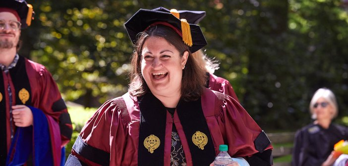 A woman in a red academic gown laughs