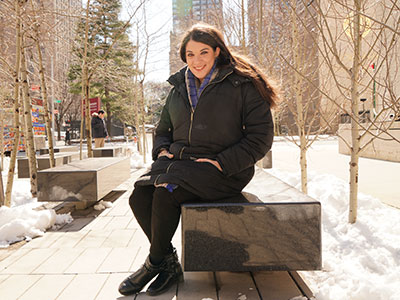 GSS graduate Allison Marino on a bench with snow on the ground