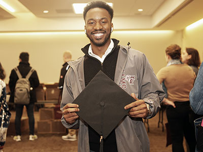 PCS graduate Tyler Brown holding a graduation cap