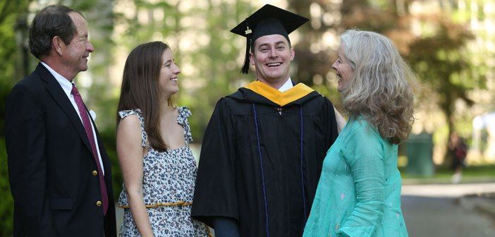 A graduate smiles for the camera as his family looks on