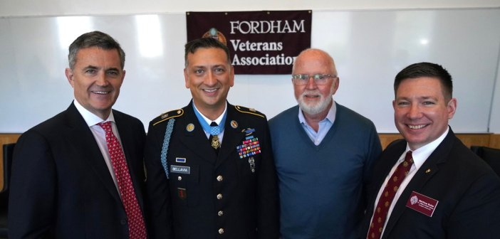 """Four men smile and stand together in front of a flag that says """"Fordham Veterans Association."""""""