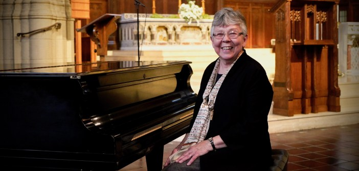 An elderly woman sits next to a piano in a church and smiles.