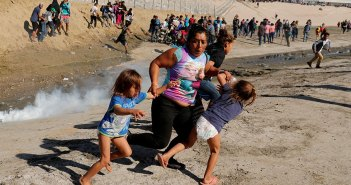 aria Meza (C), a 40-year-old migrant woman from Honduras, part of a caravan of thousands from Central America trying to reach the United States, runs away from tear gas with her five-year-old twin daughters Saira Mejia Meza (L) and Cheili Mejia Meza (R) in front of the border wall between the U.S. and Mexico, in Tijuana, Mexico, November 25, 2018.