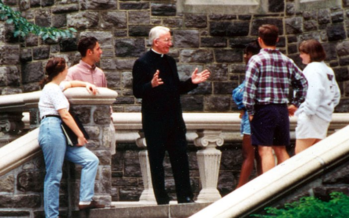Father O'Hare talking with students at Rose Hill