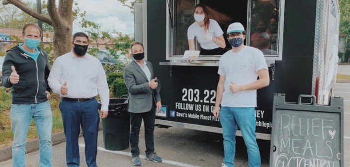 Five people standing by or in a food truck, wearing masks and giving a thumbs-up