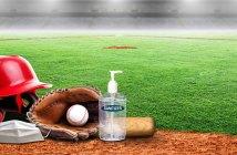 A baseball helmet, glove, and hand sanitizer on a field
