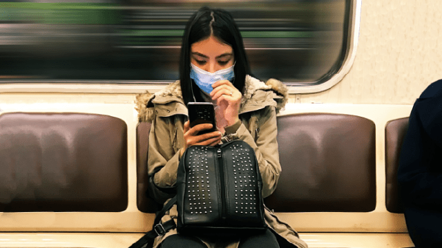 Woman wearing a mask on the subway