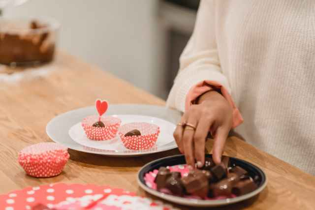 black woman taking chocolate sweets from plate near festive dessert