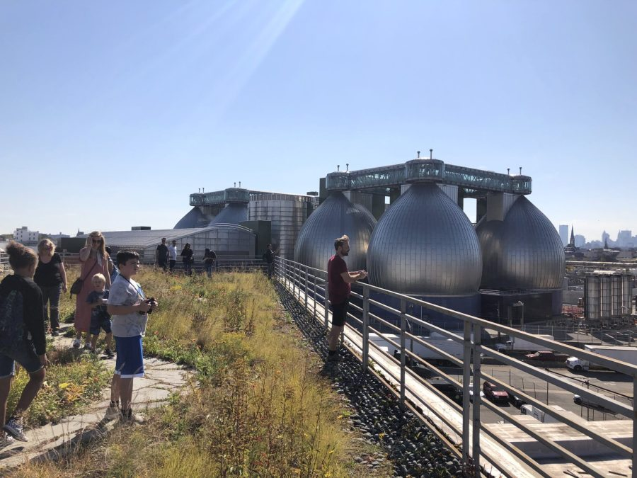 The Newtown Creek Wastewater Treatment Plant, its water-processing 'egg digesters' seen from the rooftop garden of the street art mural's building, is the city's largest sewage treatment facility. The city is making efforts to decrease its carbon emissions and waste. Gabrielle Lipton, GLF