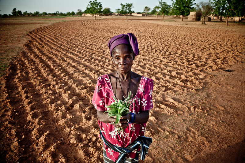A Burkinabe farmer shows the leaves she used to feed her family during a time of drought. Pablo Tosco, Oxfam