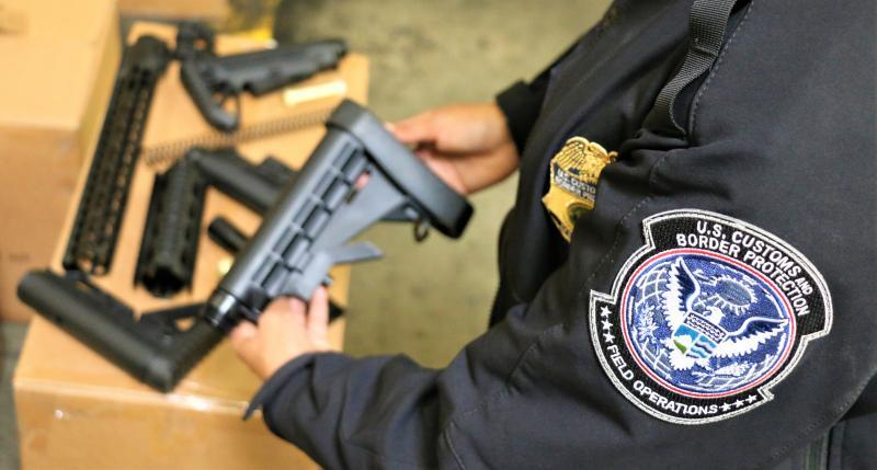 CBP officer holds gun parts