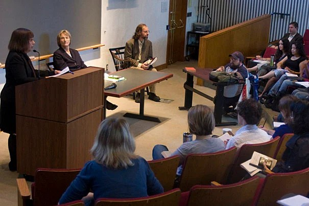 """Emily Click (standing), the Divinity School's assistant dean for ministry studies and field education, introduces President Drew Faust. Faust was the guest lecturer for """"Introduction to the Histories, Theologies, and Practices of Christianity,"""" which is co-taught by Click and Dan McKanan (seated, far right), Ralph Waldo Emerson Unitarian Universalist Association Senior Lecturer in Divinity."""