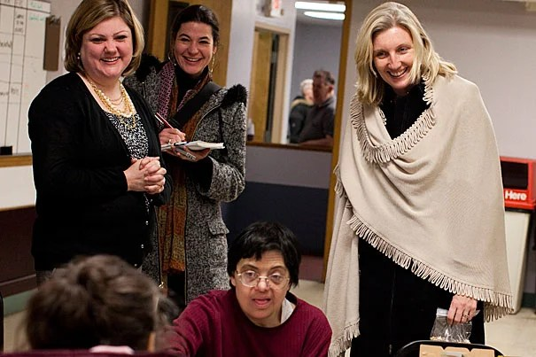 On a visit to the Vocational Advancement Center (VAC), Christine Heenan (right), Harvard's vice president of public affairs and communications, and Amy Bell (left), executive director of VAC, talk with participants in a cooking group. The VAC, which was awarded a $25,000 grant from the Harvard Allston Partnership Fund, is one of eight local nonprofit organizations to receive checks last week totaling $100,000.