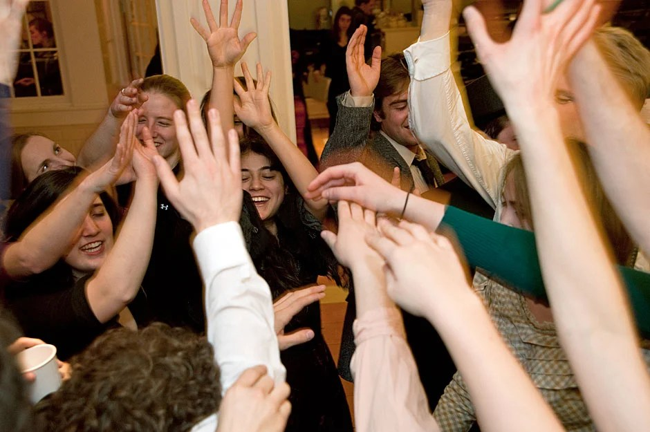 "In a show of camaraderie, Dunster House Opera Society members raise hands in a group salute before going onstage to perform Johann Strauss' ""Die Fledermaus."" Jon Chase/Harvard Staff Photographer"