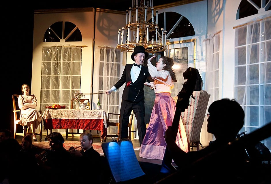 "Framed by a bass player in the orchestra, the Dunster House Opera Society performs Johann Strauss' ""Die Fledermaus"" with Ben Nelson '11 and Bridget Haile '11 in the lead roles at center stage. Jon Chase/Harvard Staff Photographer"