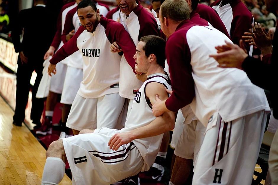 Harvard's Laurent Rivard falls into the bench...   Rose Lincoln/ Harvard Staff Photographer