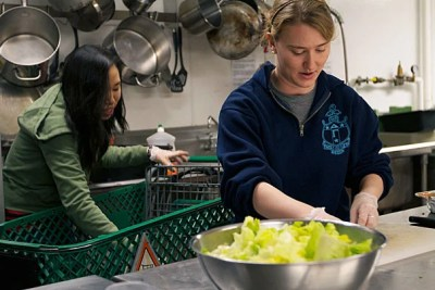 """""""As a volunteer at the Harvard Square Homeless Shelter, I feel like I'm doing something with a very tangible impact,"""" said Janie Tankard '12 (right).  Fellow volunteer Jennifer Soong '14 (left) and Tankard  prepare dinner for their guests."""