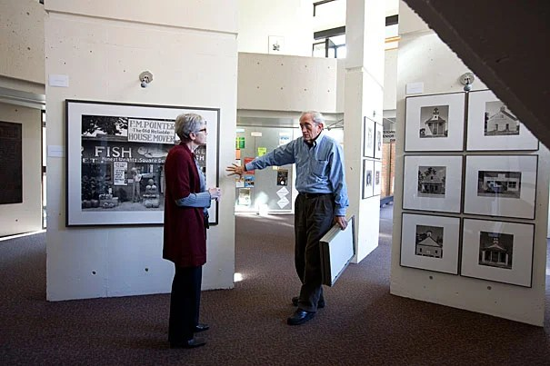 """Mather House Master Christie McDonald (left) discusses the latest exhibit with John T. Hill. Hill designed and produced """"Walker Evans: Before and After the FSA,"""" which is on view at Mather House's SNLH Three Columns Gallery."""
