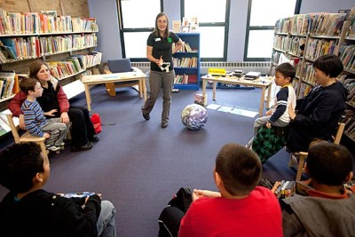 Amy Gunzelmann, education specialist at the Harvard Museum of Natural History, shows animal bones to a rapt group of kids at the Valente Branch of the Cambridge Public Library.