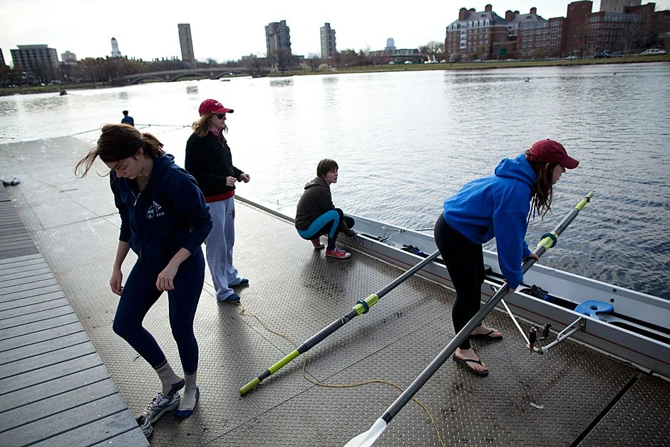 Eliot House residents who participate in the Eliot Boat Club, the intramural crew program, arrive at the boat house launch along the Charles River. Members of a women's team, including Caroline Cox '14 (from left), Brianne Corcoran, Zuzanna Wojcieszak, and Elizabeth Fryman '12, board the scull before heading out on the water. Stephanie Mitchell/Harvard Staff Photographer