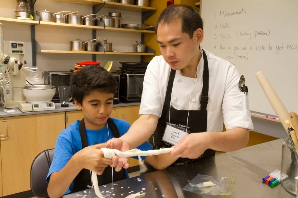Harvard hosts a two-week Science and Cooking course for Cambridge and Boston students as part of its summer learning series, bringing in top chefs from Boston and Cambridge as well as graduate students and professors from Harvard.  Jason Doo (right) assists Kays Laouar, 11, in pulling string cheese into the proper shape. Jon Chase/Harvard Staff Photographer