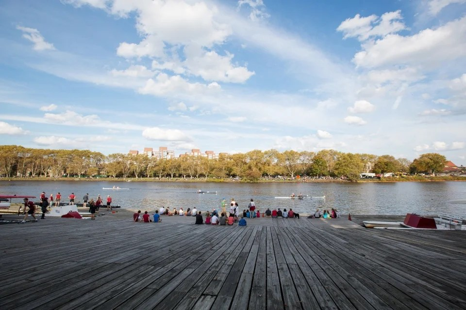 Spectators watch the Head of the Charles Regatta from the Newell Boat House dock. Harvard competed in a majority of the races on both days of the event, with participation by students, parents, alumni, and staff.