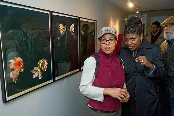 """The exhibit at the Rudenstine Gallery, featuring works by Maria Magdalena Campos-Pons (right), focuses on a selection of 20-by-24-inch Polaroid Polacolors, a medium Campos-Pons chose for its """"lusciousness."""" Joining her at the opening reception on Thursday was her student, Angela M. Counts."""