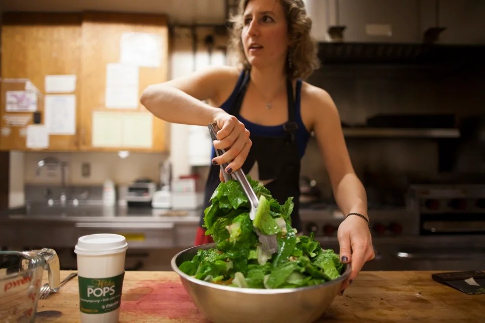 Xanthia Tucker '13 prepares the salad for the meal, tossing the lettuce with homemade vinaigrette.