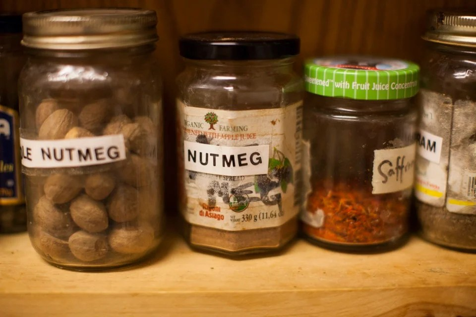 In the kitchen, spices and herbs line the shelves in an eclectic mix of recycled bottles.