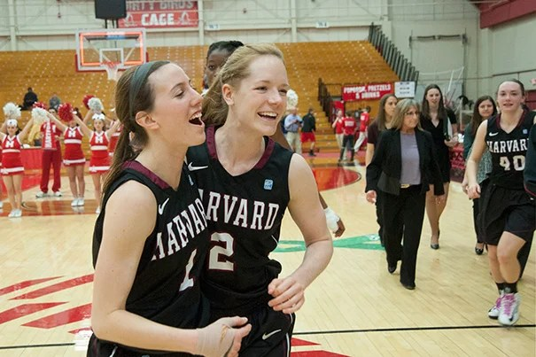 Crimson players Elle Hagedorn '13 (left) and  Melissa Mullins '14 celebrate after their 61-57 win over Hartford. Hagedorn scored Harvard's last basket of the game to seal the victory for the Crimson.