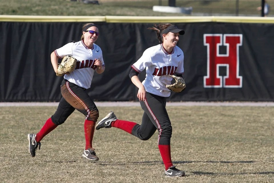 Stephanie Regan '13 (left) and Haley Davis '16 run in from the outfield at the end of the inning.