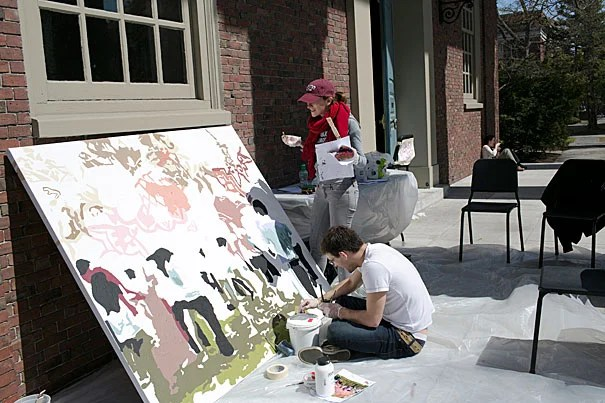 Artist Diana Gilon (standing) works with Gary Carlson '13 on a mural.