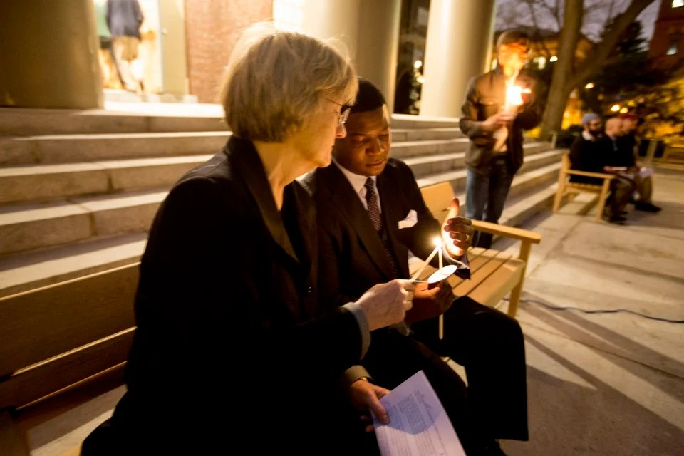 President Drew Faust and Pusey Minister Jonathan Walton light candles at the Tuesday night vigil.