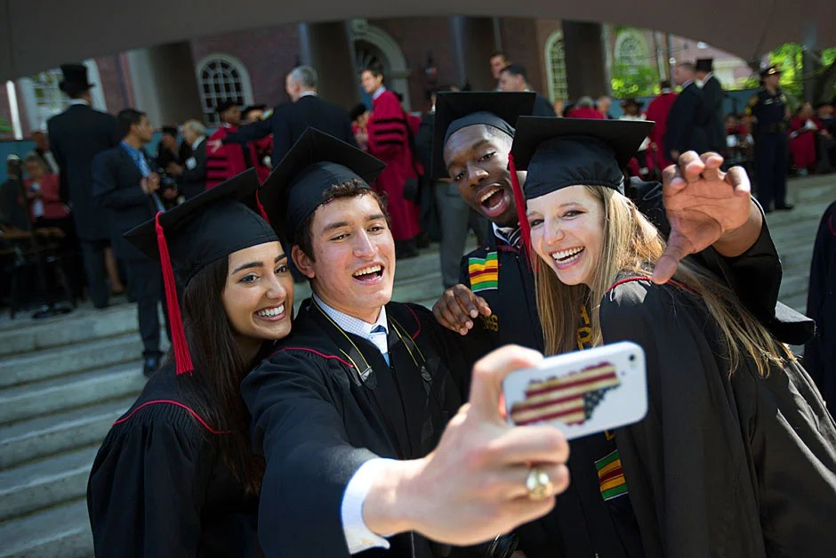 "Nadia Farjood (from left), Jose Villanueva, Everton Blair, and Margot Leger take a ""selfie"" to remember Commencement forever. Kris Snibbe/Harvard Staff Photographer"