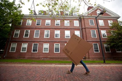 A student is eclipsed by a box while moving out from old Quincy House. Kris Snibbe/Harvard Staff Photographer